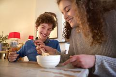 Happy brother and sister eating food - stock photo