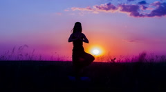 Silhouette of a Young Girl Practicing Yoga At Nature During Sunset Stock Footage