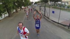 Athletes who run happy along  the riverside of Entella during the half marathon Stock Footage
