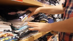 Woman Searching in Clothes Stack in Clothing Store Stock Footage
