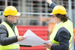 Two architects pointing at scaffolding Stock Photos