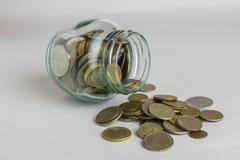Business, finance, investment, money saving -  coins in glass jar on table Stock Photos