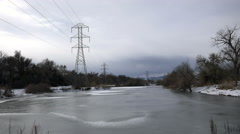 Timelapse drone buzzing around winter frozen pond cloudy industrial electric - stock footage