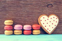 macarons and heart-shaped cookie on a blue rustic surface - stock photo