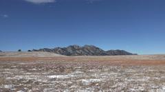 Timelapse flatiron mountains in winter snow grasslands under a blue sky. Stock Footage