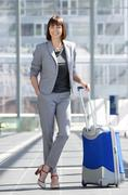 Smiling business woman standing at airport with bag - stock photo