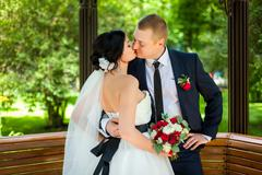 Wedding couple kissing in wooden pavilion Stock Photos