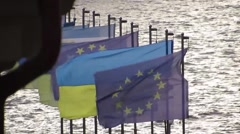 Flags of Ukraine and the EU against the backdrop of water and wind Stock Footage