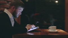 Businessman with tablet computer in the evening cafe Stock Footage
