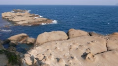 Surreal weathered rocky shore, Yehliu Geopark cape shelf, quick pan Stock Footage
