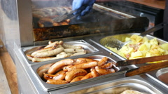 Seller laying out grilled sausages at the Christmas Fair - street food market - stock footage