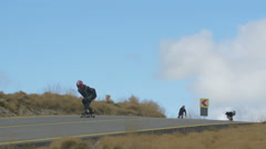 View of four longboarders riding down the road of Transalpina Stock Footage