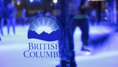People ice skating, logo of British Columbia on transparent glass Stock Footage