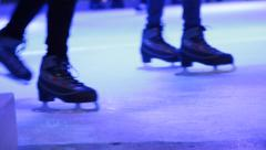Stock Video Footage of Ice skaters on skating rink, legs in frame, closeup
