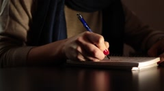 Young woman, red nails handwriting, dark backgound Stock Footage