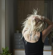 Young woman with hands in hair revealing back tattoos Stock Photos
