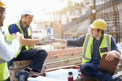 Construction workers and engineer enjoying coffee break at construction site Stock Photos