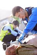 Stock Photo of Rescue worker using defibrillator on unconscious car accident victim in road
