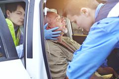 Stock Photo of Rescue workers carefully tending to car accident victim in car