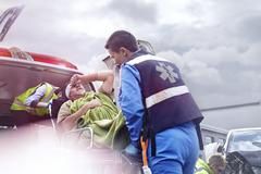 Rescue workers loading car accident victim into back of ambulance Stock Photos