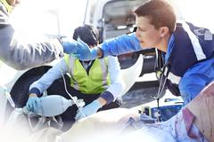Stock Photo of Rescue workers with manual resuscitator over car accident victim in road