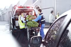 Rescue workers tending to car accident victim on stretcher at back of ambulance - stock photo