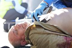 Rescue worker using defibrillator on unconscious car accident victim Stock Photos