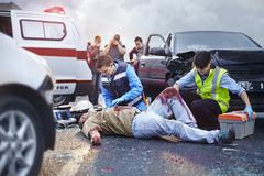 Rescue workers tending to bloody car accident victim in road - stock photo