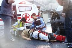 Rescue workers tending to car accident victim in road - stock photo