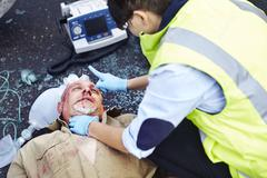 Stock Photo of Rescue worker tending to car accident victim in road