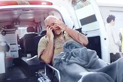 Distressed man on stretcher talking on cell phone behind ambulance - stock photo