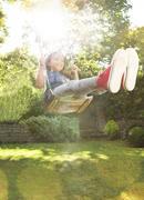 Enthusiastic girl swinging in sunny backyard Stock Photos
