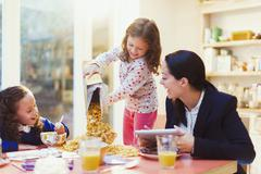 Girl pouring abundance of cereal at breakfast table Stock Photos