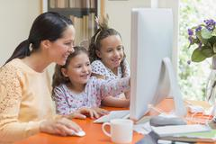 Mother and daughters using computer Stock Photos
