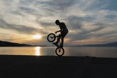 Biker jumping with the sunset as background. Stock Photos