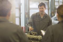 Mechanic explaining engine to students in auto repair shop Stock Photos