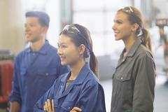 Smiling mechanics looking away in auto repair shop Stock Photos