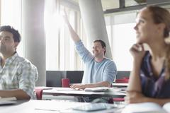 Eager man raising hand in adult education classroom Stock Photos