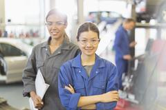 Portrait confident female mechanics in auto repair shop Stock Photos