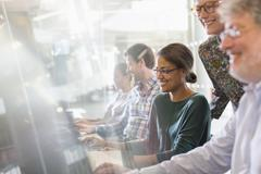 Students at computers in adult education classroom - stock photo
