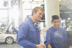 Smiling mechanics using computer in auto repair shop Stock Photos