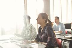 Attentive students listening in adult education classroom - stock photo