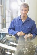 Portrait confident mechanic working on engine in auto repair shop - stock photo