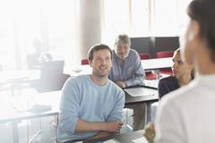 Professor and students talking in adult education classroom Stock Photos