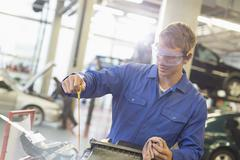 Mechanic checking engine oil in auto repair shop - stock photo