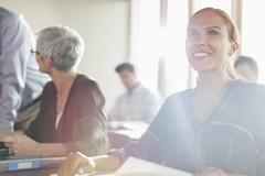 Smiling woman in sunny adult education workshop - stock photo