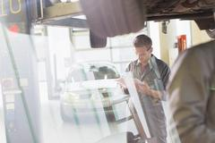 Mechanic with clipboard under car in auto repair shop Stock Photos