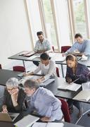 Students studying in adult education classroom - stock photo