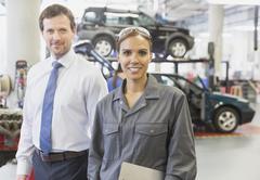 Portrait confident businessman and female mechanic in auto repair shop Stock Photos