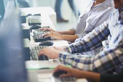 Students typing at computers in adult education classroom - stock photo